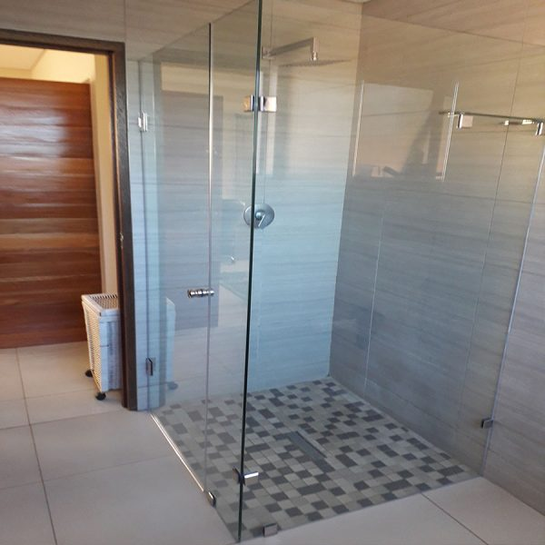 Frameless Door Hinging On The Wall With An In-line Panel and Return Panel With Stabilizing Glass Shelf