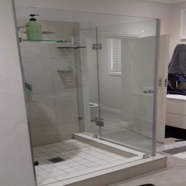 Frameless shower enclosure with door hinging off a panel