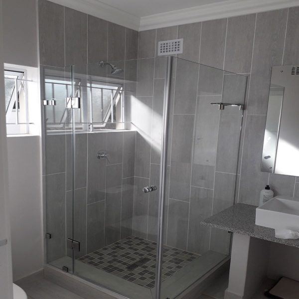 Square frameless door hinged off in line panel with return